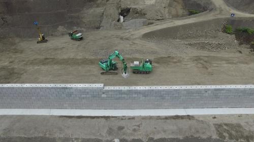 ダンプトラックが運んできたブロックを、バックホーに装備したカメラで認識して自動で設置する(写真:鹿島)