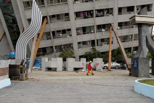 敷地の外、南側から地面と低層部を撮影。建物南側は4階が地面に接している状態だ。地面はひび割れ、粉々に砕けた窓のガラスが散乱していた(写真:菅原 由依子)