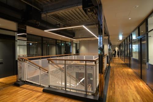 革張りの手すりがついた階段を上ると2階オフィスフロアがある。10~40m2の個室があり、スモールオフィスや会議室として貸し出す。会議室は30分当たり2200~4000円で利用できる(写真:菅原 由依子)