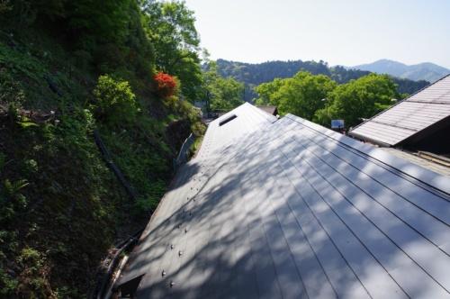高尾山スミカの後ろに山の斜面が迫る。通路と山に挟まれた狭小空間でのプロジェクトだった(写真:日経アーキテクチュア)