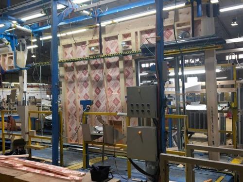 〔写真1〕プレカットした木材を使ってパネルを製造。サッシや断熱材の取り付け、防水紙の施工など、大工が現場で行う作業を工場で完了させる(写真:ウッドステーション)