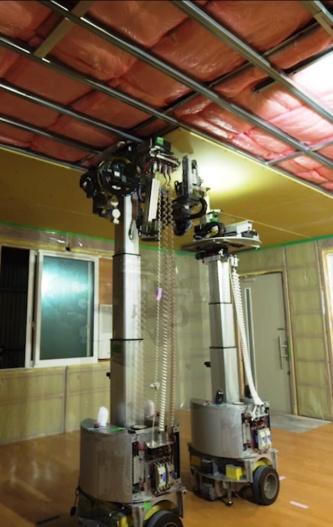 積水ハウスが2020 年の実用化を目指す天井施工ロボット。AIを搭載した2 台のロボットが連携して作業する。産業用ではなく、介護や福祉の現場などで使われているサービスロボットをベースに開発した(写真:積水ハウス)