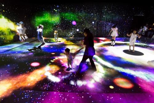 『マルチジャンピング宇宙 / Multi Jumping Universe』。「この空間で人々は、時空世界のひずみをつくります。そして、そのひずみが、宇宙空間の星屑(チリ)とガスを引き寄せ、星を誕生させたり、星を成長させたりします」(写真:森ビル デジタルアート ミュージアム:エプソン チームラボ ボーダレス/チームラボ)