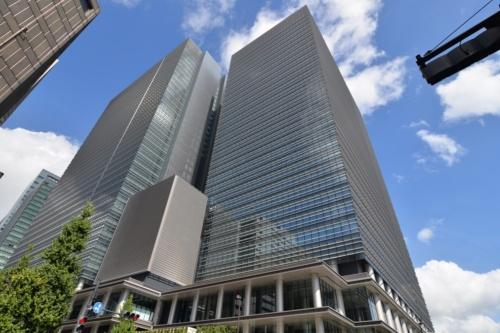 東京・大手町に8月完成した「大手町プレイス」を南東側から見上げる。写真奥が地下3階・地上35階建てのウエストタワー、手前が地下3階・地上32階建てのイーストタワー。2棟を低層部で連結する構造だ。外装にみられる水平庇やアルミ丸柱は、以前この地にあった逓信ビルの意匠を意識したもの(写真:日経アーキテクチュア)