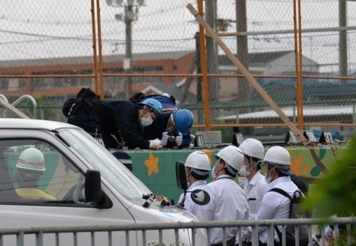 大阪北部地震で倒壊した高槻市立寿栄(じゅえい)小学校のブロック塀。警察官などが現場検証している様子。地震直後の2018年6月19日に撮影したもの。現在も業務上過失致死の疑いで大阪府警の捜査が続く(写真:日経アーキテクチュア)