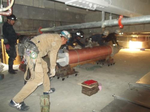 鳥取県立中央病院の免震層から不正ダンパーを搬出する様子。写真中央の筒がダンパーで、約1.3トンある。オレンジ色の養生シートで覆って台車に載せ、人力で動かした。免震層は配線や配管が入り組んでおり、かがまなければ通り抜けられない(写真:鳥取県)