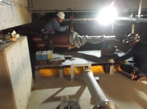 鳥取県立中央病院の免震層から不正ダンパーを搬出する様子。地面側には約2万ボルトの高圧電線が配線されており、段差ともなっていた。配線を覆う形で鋼製の架台を設置、架台の上を滑らせる形で通過させた(写真:鳥取県)