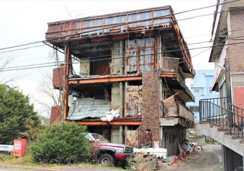 滋賀県野洲市に立つ老朽化した空き家マンション「美和コーポ」。2018年6月の大阪北部地震や、その後の18年8月と9月の台風で外壁などが崩落して危険な状態が続いている。市は19年3月18日、区分所有者に対して自主解体を求める命令書を送付した(写真:日経アーキテクチュア)