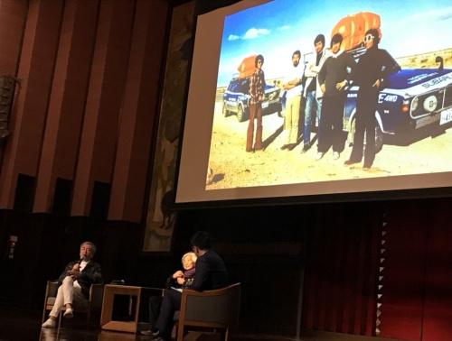 後ろに投映された写真は、隈氏が大学院時代に原氏に同行した西アフリカでの集落調査のスナップ。車2台でサハラ砂漠を駆け抜けた。右端が原氏、中央が隈氏(写真:日経アーキテクチュア)