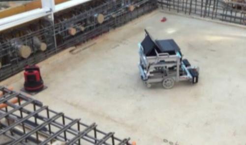 墨出し作業の様子。測量機(左)と竹中工務店が開発したロボット(右)を組み合わせて使用する(写真:竹中工務店)