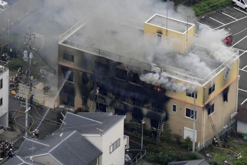 煙を上げるアニメ制作会社「京都アニメーション」の第1スタジオ。屋内に2つあった階段や窓を伝った外壁から急速に延焼したとみられる=18日午前11時36分(写真:共同通信社)
