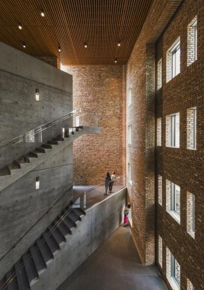 エントランスを入ると3層吹き抜けのアトリウムが広がる。コンクリートの大きな階段とレンガの壁の対比が象徴的(写真:Jeff Goldberg/Esto)