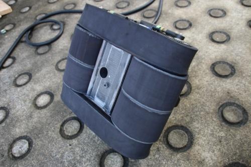 壁面走行ロボットの裏側。中央に配置したバキュームチャンバーで空気を吸引して壁面に吸い付き、吸引口周りのローラーの回転で走行する(写真:高松建設)
