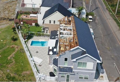 館山市西川名地区に立つ築20年の木造2階建て住宅では、母屋と垂木が飛散した。接合金物は確認できなかった。海岸に面する側の窓ガラスも割れた(写真:早川 由紀夫)