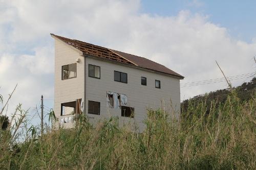 館山市西川名地区に立つ混構造の3階建て住宅は開口部と外装材が壊れ、小屋組みが飛散していた。構造計算が必要な建物だ(写真:日経 xTECH)