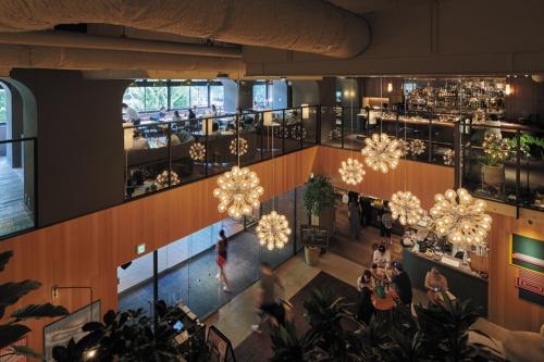 2階レストランから見下ろしたエントランスの吹き抜け。ペンダント照明や床のタイルなど、クラシックな雰囲気の既存のエレメントを残している。入ってすぐの場所に、新規開業したベーカリーのティースタンドがある(写真:山本育憲)