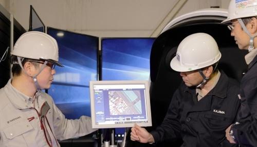 建設機械を遠隔操作するシステムの効果を実証する様子。名古屋市にあるタワークレーンを大阪市から遠隔操作した(写真:鹿島、竹中工務店)