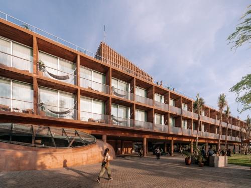 ホテルの西側ファサード。ピロティーの上に「フローティング・リング」と呼ぶ客室階が載る(写真:Kevin Mak)
