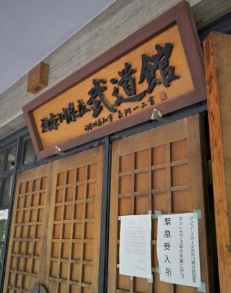 県立武道館の入り口には「緊急受入所」の張り紙があった(写真:日経アーキテクチュア)