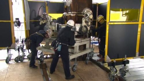 専用台車を使ってロボットを設置している様子。ロボットの総重量は100kg弱で、通常は2人で設置することを想定している(写真:鹿島)