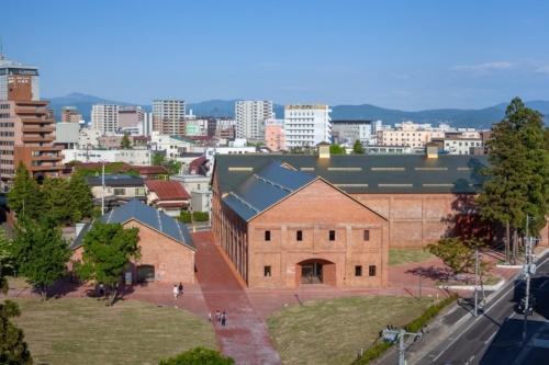 青森県弘前市に完成した「弘前れんが倉庫美術館」。右が「ミュージアム棟」、左が「カフェ・ショップ棟」。菱ぶきの屋根にはチタンを使用している(写真:吉田 誠)