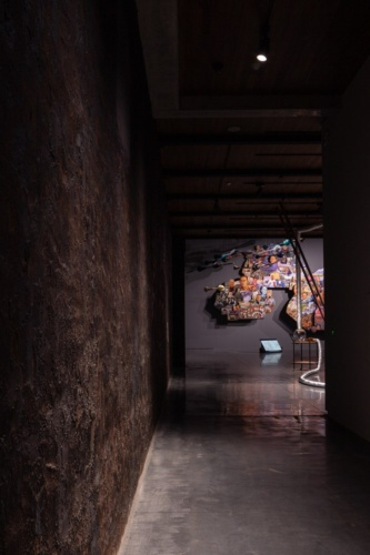 一部の展示室では、既存壁のコールタールの風合いをそのまま生かした。奥の壁に写るのは、ナウィン・ラワンチャイクン氏の作品「いのっちへの手紙」(写真:吉田 誠)