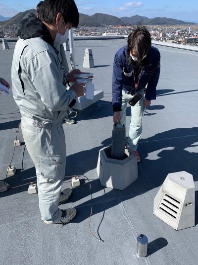 マンション屋上の通気口から試験ボールを投入しているところ(写真:長谷工コーポレーション)