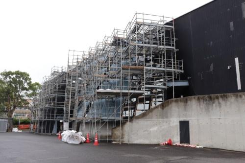 雨漏り対策で板張りの外壁とガラス面の大半を鋼板で覆う工事を進める熊本県苓北町の町民ホール。2020年6月18日撮影(写真:日経アーキテクチュア)