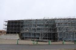 左が竣工当時、右が改修工事中の南側外観。写真右手の外壁が大きく張り出した開口部分に階段と出入り口がある。波状の外観と、大きなガラス面が特徴だ(写真:左は安川 千秋、右は日経アーキテクチュア)