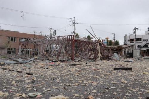 爆発が起こった店舗の様子。外壁や屋根が吹き飛び、鉄骨の架構のみになった。周辺には大量のがれきが飛散した。向かいにある東邦銀行(写真左手)ではガラス破損など大きな被害が出た(写真:郡山地方広域消防組合)