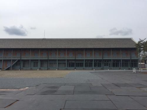 西置繭所の東側外観。9月29日に撮影。操業が最盛期にあった1970年代の外観に復旧させた。屋根はいったん瓦を下ろしてふき直した。施設見学者が目にする東面の屋根には当初から使われた瓦を用いた。レンガは当初からのものだが、アラミドロッドを埋め込んだ箇所が白い帯となって見える(写真:日経アーキテクチュア)