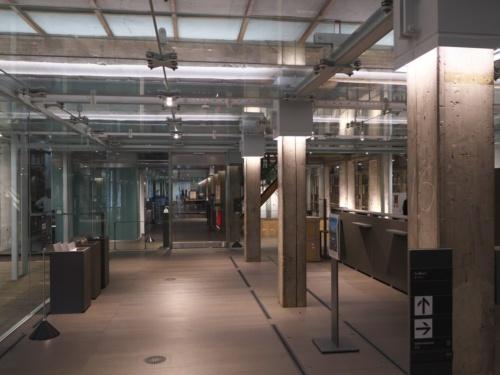 1階に新設したインフォメーション。通し柱に圧着した鋼製部材は、柱との隙間を無収縮モルタルで充てんしている。天井のガラス面も構造の一部だ(写真:池谷 和浩)