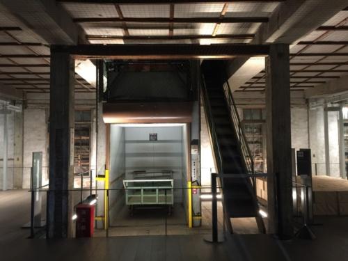1階、入ってすぐの場所にかつて使われていたリフトがある。そのまま展示している(写真:日経アーキテクチュア)