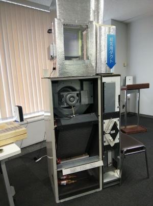 記者会見場に展示された「新・エアロテック-UV」の屋内機。熱交換や空調を行うユニットの上に「新・UVクリーンユニット」を載せている(写真:池谷 和浩)