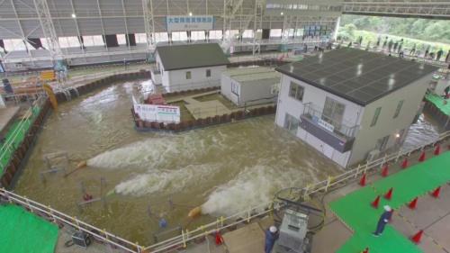 水深3mでの浸水実験の様子。奥が一般仕様の住宅で、2階バルコニーの下まで水に漬かっている。右が耐水害住宅で、1階高さの半分が水に漬かった状態で浮いている(写真:一条工務店)
