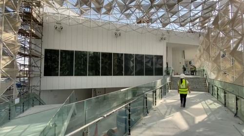 両側にガラスの手すりがあるスロープを上り、日本館の建物に向かう永山氏(写真:永山祐子建築設計、20年11月29日時点)