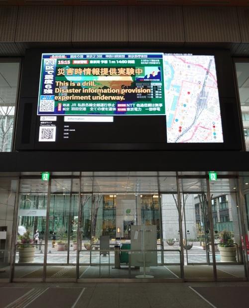 丸ビル1階の巨大なデジタルサイネージに表示された「災害ダッシュボード4.0」の画面(写真:日経クロステック)