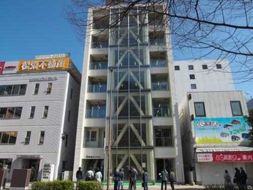 完成した純木造「高惣木工ビル」。JR仙台駅東口ロータリーの正面という好立地だ。2021年3月4日から実施した見学会には建築関係者、木材関係者などが詰めかけた。ブレースは金属製で、木材で覆っている(写真:池谷 和浩)
