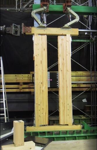 制振と耐震という2つの性能を兼ね備えるエンダーウォールを、水平加力試験機で加力している様子。木質フレームの中央に見える黒い部分が制振装置「KOAダンパー」。KOAダンバーに付けたピンクの印は変形量を示す(写真:日経アーキテクチュア)