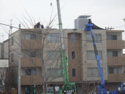 2021年3月10日に札幌市内で吹き荒れた強風で、屋上から断熱防水層が剥がれたとみられる同市西区に立つRC造の賃貸マンション。複数の作業員がクレーンを使って、屋上の断熱防水層を撤去している。札幌市消防局に被害が通報されてから約7時間後の午後4時50分ごろに撮影(写真:栃木 渡)