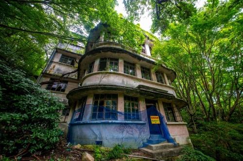 旧摩耶観光ホテルの外観。樹木に囲まれ、現在は摩耶ケーブル虹の駅か、東側の登山道から徒歩でアクセスするしかない。内部は立ち入り禁止で、ツアーを利用すれば外観を見学できる(写真:前畑洋平・温子)