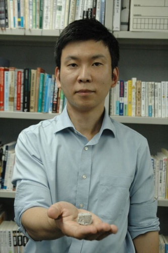 砂同士を接着した硬化体を持つ東京大学生産技術研究所の酒井雄也准教授(写真:日経クロステック)