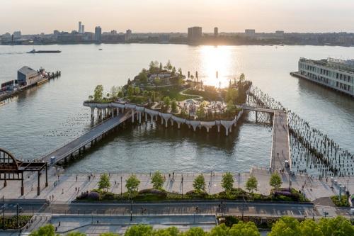マンハッタン西側の遊歩道ハドソン・リバー・グリーンウェイ越しに見た「リトルアイランド」。ハドソン川には台風で大破したピア54の木杭が残され、現在は漁礁になっている。左手に突端が見えるガンズヴォート・ペニンシュラも22年に緑地公園としてオープンする予定だ。造園デザインはジェームズ・コーナー・フィールド・オペレーションが担う(写真:Timothy Schenck)