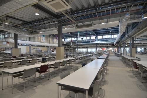 メインダイニングホールの2階。天窓から光が入り、明るい印象だ。感染対策のため、当初の予定より椅子の数を大幅に減らした。利用時には、アクリル板のパーティションをテーブルの上に設置する(写真:日経アーキテクチュア)
