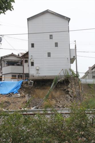 基礎下の地盤と擁壁が崩落した状態で倒壊を免れた戸建て住宅。6月26日に撮影(写真:日経クロステック)