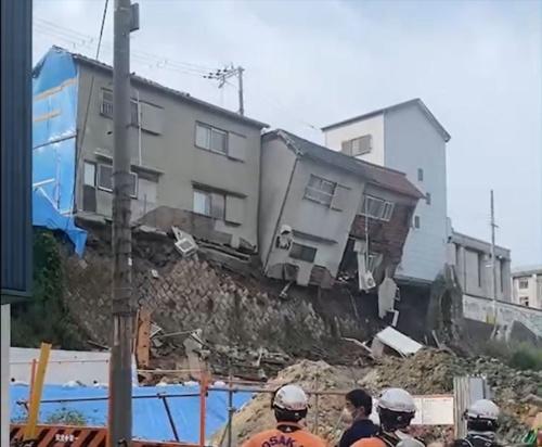 空石積み擁壁が上部から崩れ始め、住宅が転落しつつある様子。隣接する3階建ての戸建て住宅(写真右側)を支える擁壁と地盤も、上部が先に崩落している(写真:住民提供)
