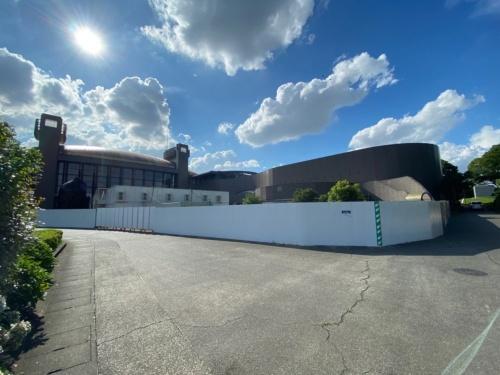 浸水被害を受けた後の川崎市市民ミュージアムの外観。被災後は囲いを設置し、一般の人が立ち入れないようにしている。囲いの内側にはプレハブやコンテナを設置し、この中で収蔵品の応急処置や保管をしている(写真:川崎市)