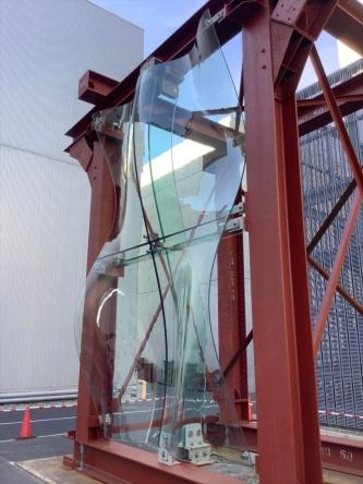 縦5m×横3mの実大モックアップ。4枚のガラスが集まる中央付近に、金属3Dプリンターで製作した点支持部材が見える。新構法では、表面のガラスを支える背面のリブもガラスにして、ファサード全体の透明感を高めている(写真:清水建設)