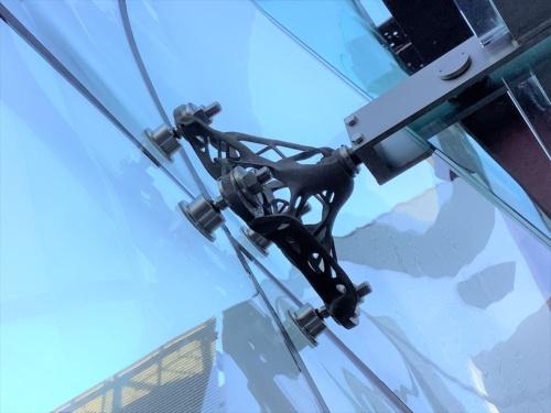3次元曲面ガラススクリーン構法では、ガラスを点支持する。ガラス部材と支持金物の接合点はシリコン系の接着剤で固定し、施工精度を確保しながら取り付けの手間を減らした(写真:清水建設)