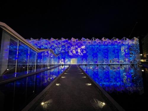 青くライトアップした日本館。夜も水盤にファサードが映り込み、建物が実物よりも大きく見える(写真:永山祐子建築設計)